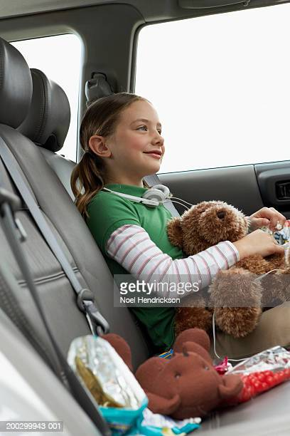Girl (6-8 years) sitting with soft toys on rear seat of car, smiling, side view