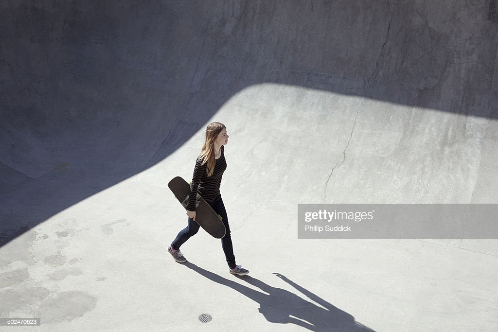 Girl skateboarder walking through a concrete bowl