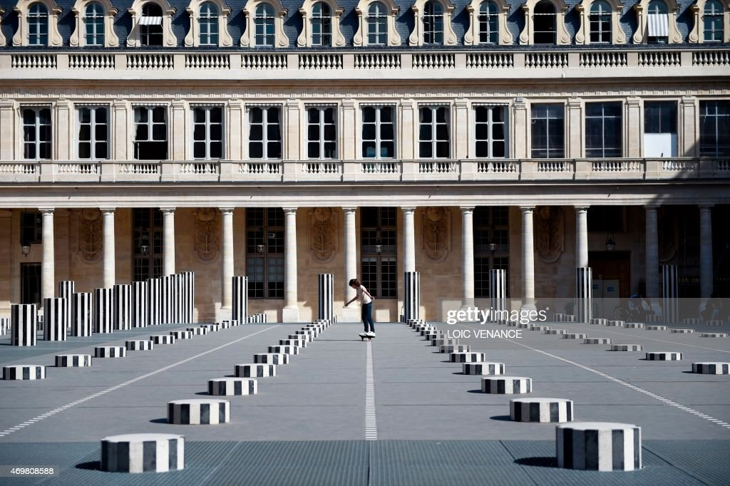 A girl skateboards in Les Deux Plateaux also known as the Colonnes de Buren in the gardens of the Palais Royal in Paris on April 15 2015 AFP PHOTO /...