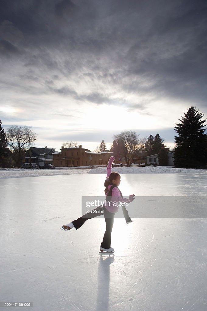 Girl (11-13) skating on frozen lake, sunset, winter : Stock Photo