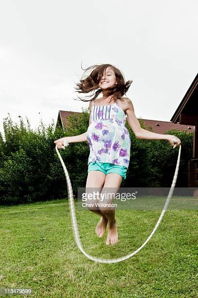 Girl skipping in garden