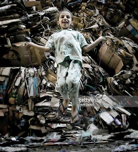 Girl (6-7) skipping rope in garbage heap
