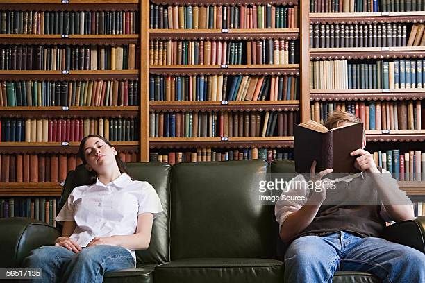 Girl sleeping and boy reading in the library