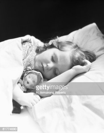 Girl sleeping, head on pillow, baby doll toy under arm. : Stock Photo