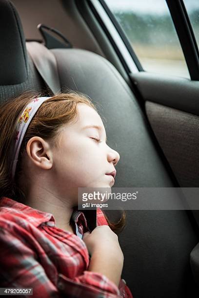 Girl (7) sleeping in backseat of car