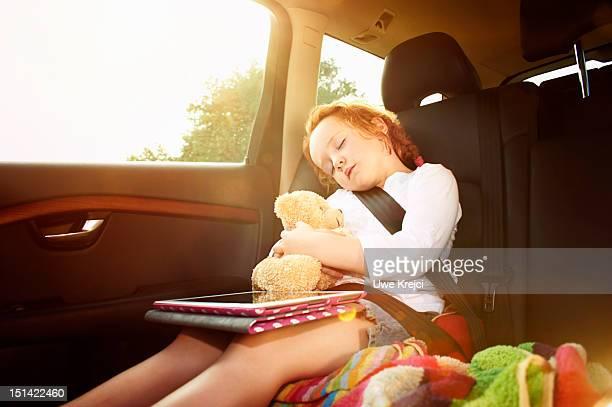 Girl (4 - 6 years) sleeping in rear seat of car