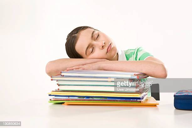 Girl sleeping on a pile of exercise books and school books