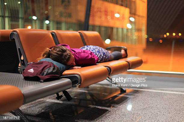 A Girl Sleeping On Chairs At An Airport