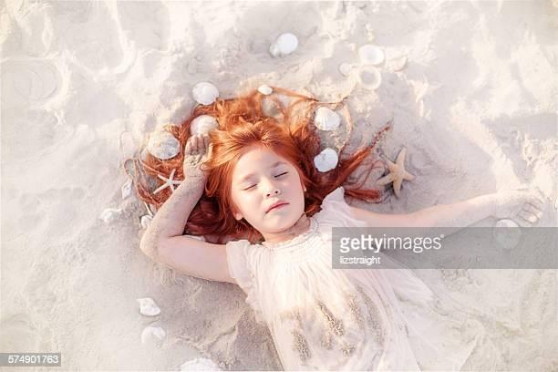 Girl sleeping on the beach with seashells in her hair