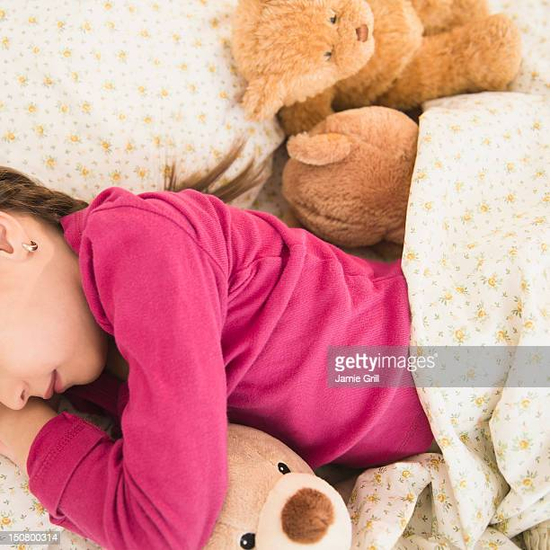 Girl sleeping with teddy bears