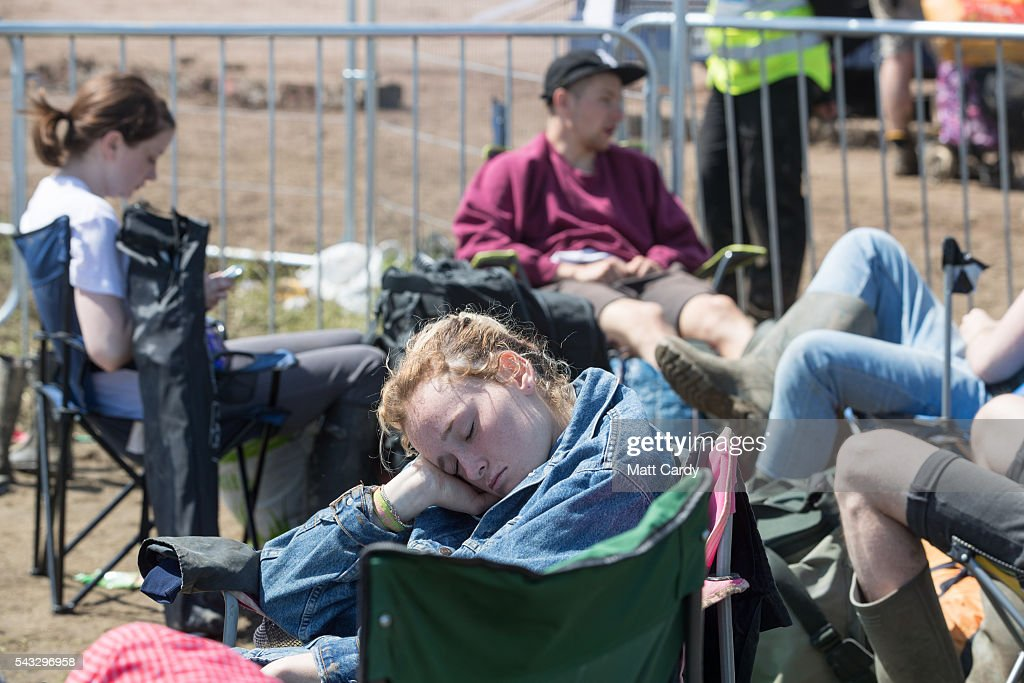 A girl sleeps as she waits for a bus as festival goers leave the Glastonbury Festival 2016 at Worthy Farm, Pilton on June 26, 2016 near Glastonbury, England. The Festival, which Michael Eavis started in 1970 when several hundred hippies paid just £1, now attracts more than 175,000 people.