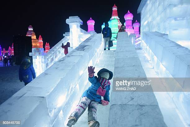 A girl slides at the China Ice and Snow World during the Harbin International Ice and Snow Festival in Harbin northeast China's Heilongjiang province...
