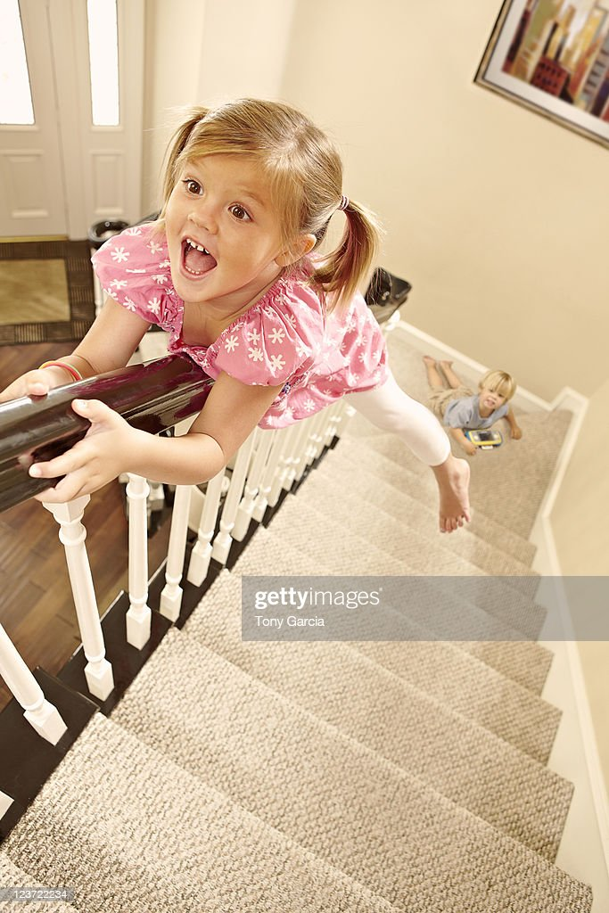 Girl sliding down banister. : Stock Photo