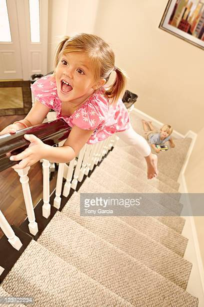 Girl sliding down banister.