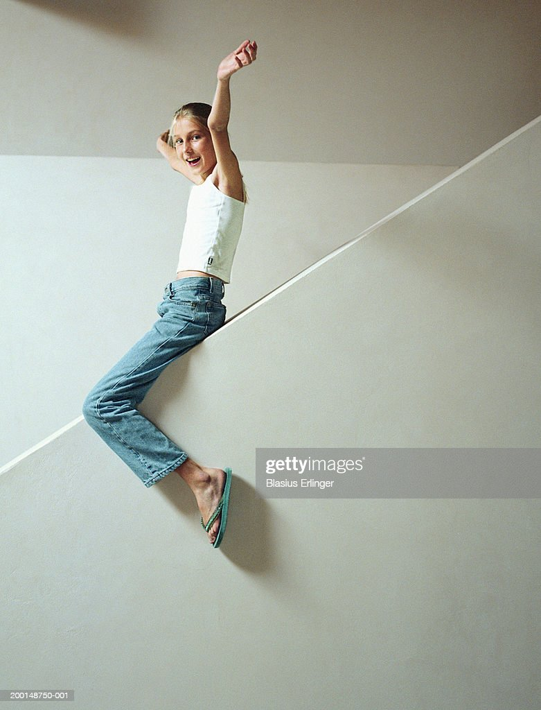 Girl (10-12) sliding down banister wall with arms in air, portrait