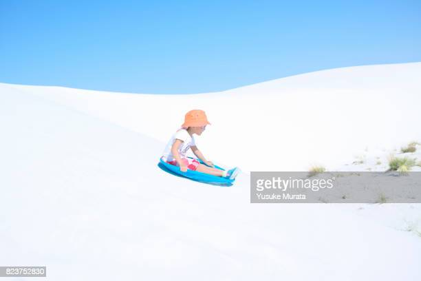 Girl sliding down sand dune