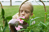 Girl smelling mandevilla blossoms