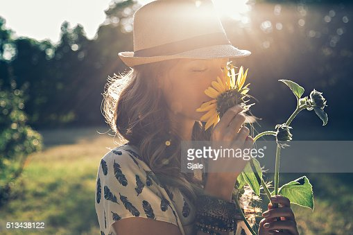 Girl smells sunflower : Stock Photo