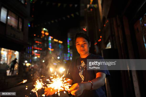A girl smiles as holding beautiful sparklers in hands during Laxmi Puja as the procession of Tihar or Deepawali and Diwali celebrations at Kathmandu...