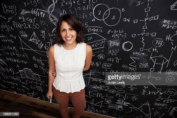 Girl smiles by a chalkboard of math
