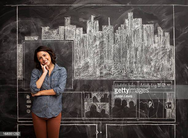 Girl smiles in front of chalkboard facebook page