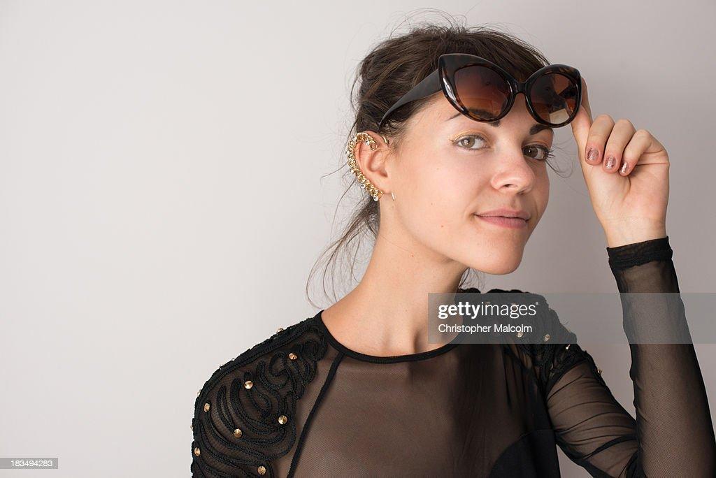 Girl smiles while lifting sunglasses : Stock Photo