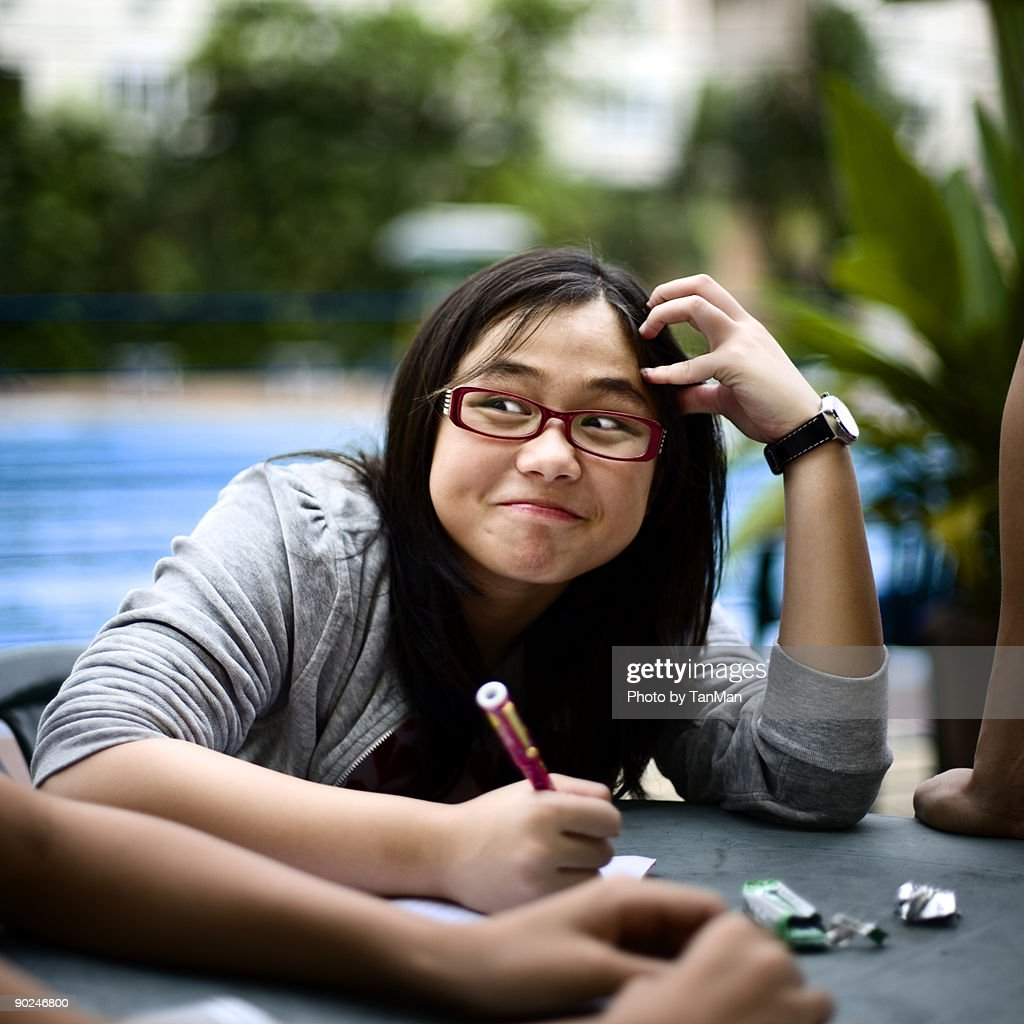 Girl smiles while writing her assignments.