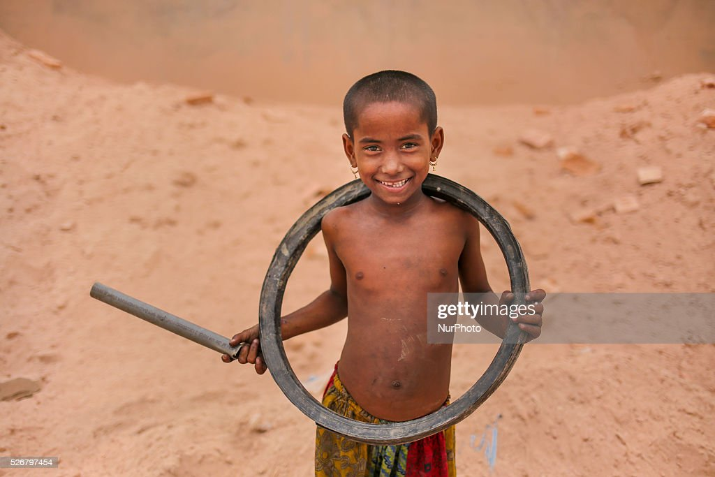 A girl smiles with a bicycle tyre which is a toy for her. She plays with it. Brickfield is a place where hundreds of children live with their working parents and growing up here in dusty environment and without any kind of formal education which is leading them towards uncertain future.