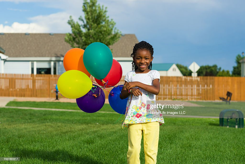 Girl Smiles with colorful balloons : Stock Photo