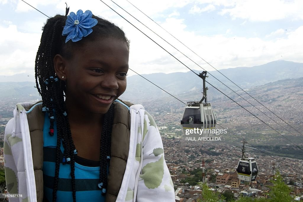 "A girl smiles with the Metrocable behind her, in Santo Domingo Savio neighbourhood in Medellin, Antioquia department, Colombia on March 1, 2013. Medellin, which competed with New York and Tel Aviv, was chosen by popular vote through the internet, as the ""Innovative City of the Year"" during the City of the Year contest, organized by The Wall Street Journal and Citigroup. The distinction was basically made for its modern transportation system, its public library, escalators built in a shantytown and schools that have allowed the integration of society. AFP PHOTO/Raul ARBOLEDA"