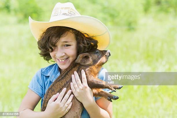 Niña sonriente y sosteniendo un lindo bebé cerdo