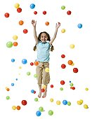 A girl smiling and playing with colored balls