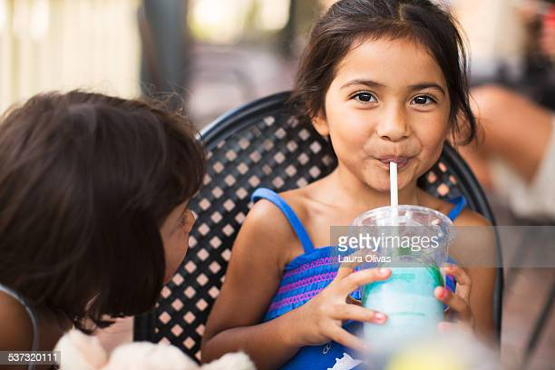 Girl Smiling As She Drinks From A Straw