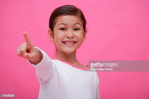 Girl smiling at camera, pointing a finger