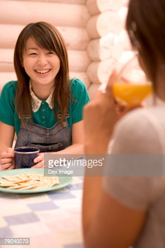 Girl smiling at friend across the dining table : Stock Photo