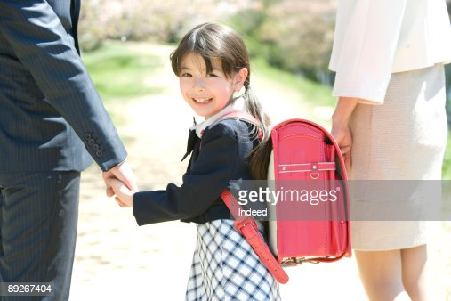 Girl (8-9) smiling, holding hands with parents