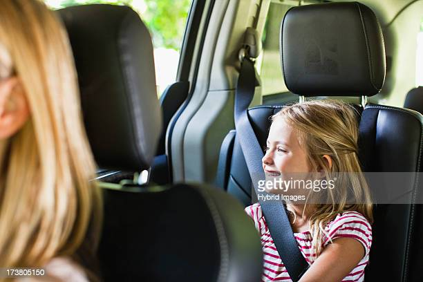 Girl smiling in backseat of car