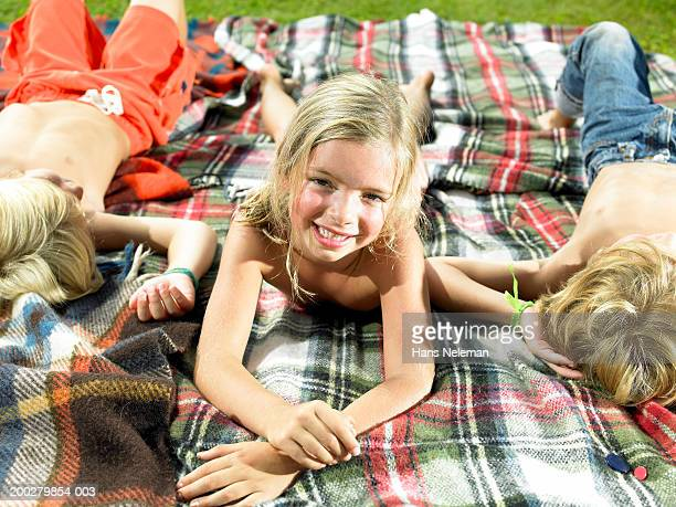 Girl (5-7) smiling on blanket in backyard, portrait