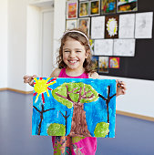 Girl smiling to camera showing her painting