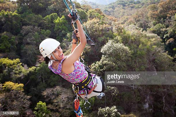 Girl smiling while riding a zip line over tree top