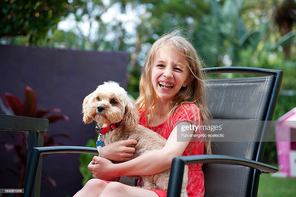 Girl smiling with dog on her lap : Stock Photo