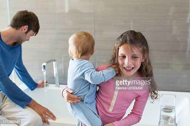 Girl smiling with her brother and her father sitting on a bathtub rim in a bathroom