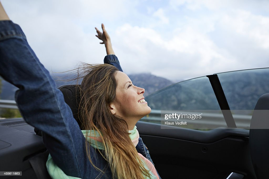 Girl smiling with raised arms, riding car : Stock Photo