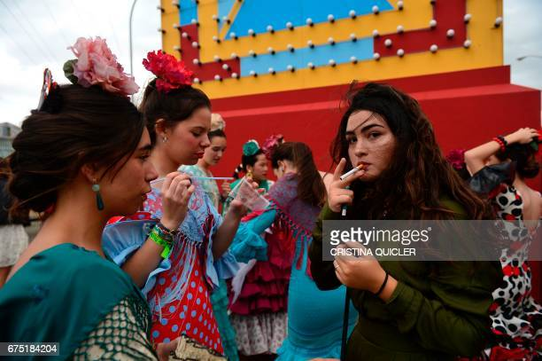 A girl smokes a cigarrette beside others wearing traditional Sevillian dresses during the 'Feria de Abril' in Sevilla on April 30 2017 The fair dates...
