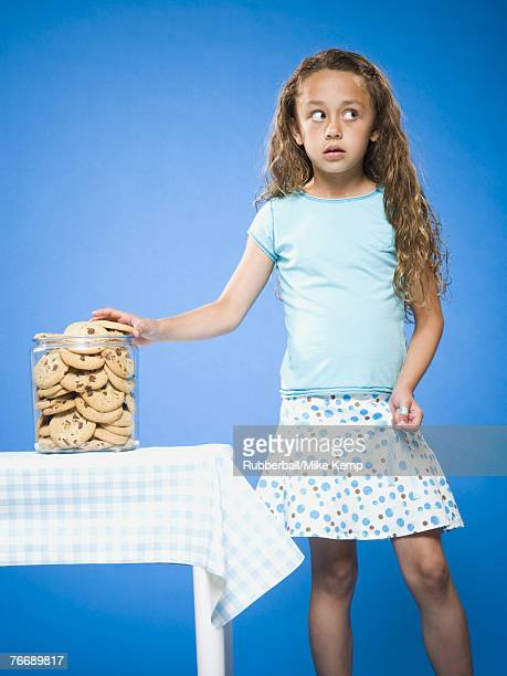 Girl sneaking Chocolate Chip Cookie from cookie jar