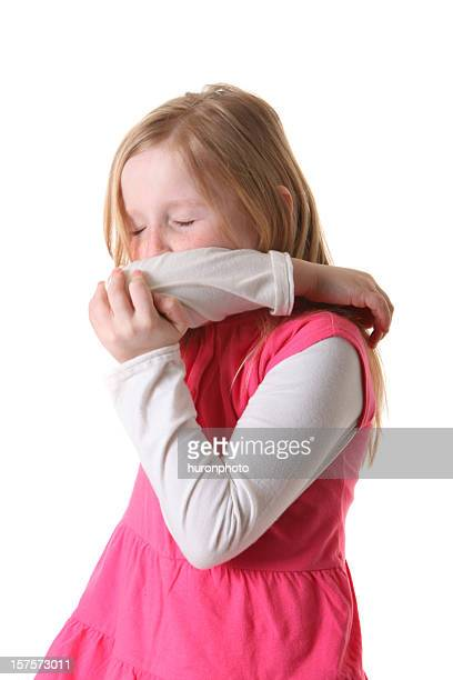 girl sneezing into arm