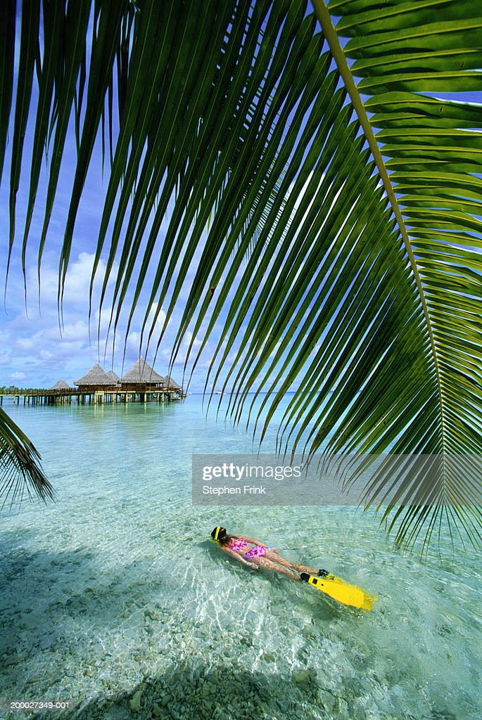 Girl (9-11) snorkeling in shallow waters, elevated view