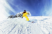 Girl snowboarder moving fast from off-piste slope. Backcountry ski and snowboard resort Sheregesh.