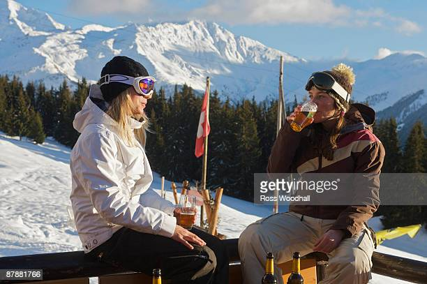 Girl snowboarders having apres beers