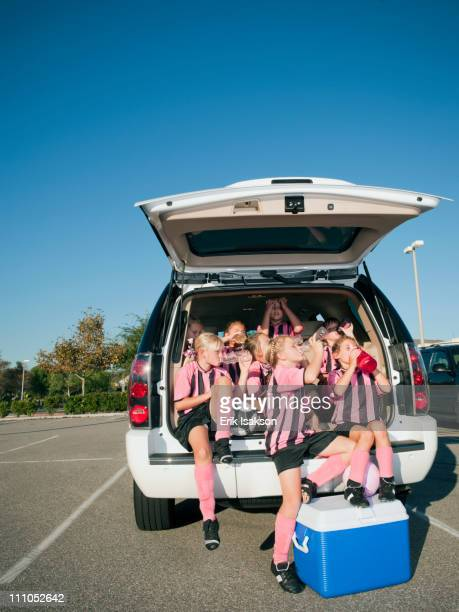 Girl soccer players sitting in back of car